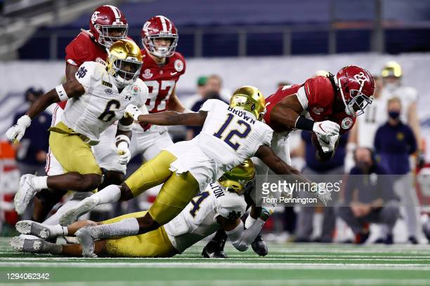 Running back Najee Harris of the Alabama Crimson Tide carries the football over safety DJ Brown of the Notre Dame Fighting Irish during the fourth...