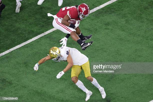 Running back Najee Harris of the Alabama Crimson Tide leaps cornerback Nick McCloud of the Notre Dame Fighting Irish during the first quarter of the...