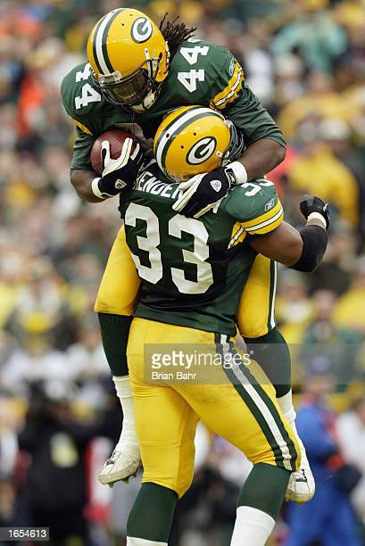 Running back Najeh Davenport of the Green Bay Packers jumps into the arms of fullback William Henderson after scoring during the NFL game against the...
