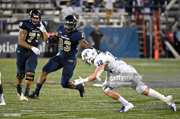 FIU running back Napoleon Maxwell evades Middle Tennessee safety Reed Blankenship while carrying the ball in the fourth quarter as the FIU Golden...