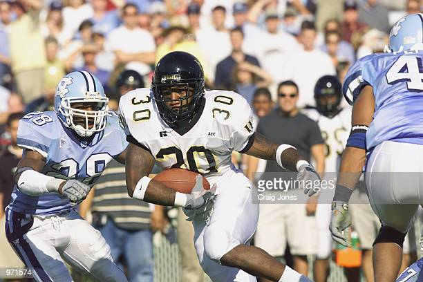 Running Back Nick Burney of the Wake Forest Demon Deacons carries the ball against safety BillyDee Greenwood the North Carolina Tar Heels during the...
