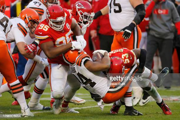 Running back Nick Chubb of the Cleveland Browns is tackled by middle linebacker Anthony Hitchens and defensive tackle Chris Jones of the Kansas City...