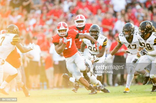 Running back Nick Chubb of the Georgia Bulldogs escapes a tackle by defensive back Clifton Duck of the Appalachian State Mountaineers at Sanford...