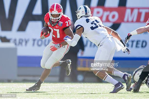 Running back Nick Chubb of the Georgia Bulldogs looks to maneuver by linebacker Sammy Douglas of the TCU Horned Frogs at Liberty Bowl Memorial...