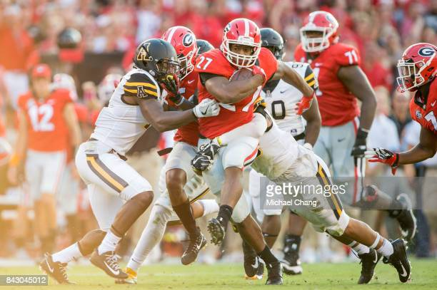 Running back Nick Chubb of the Georgia Bulldogs runs the ball through traffic during their game against the Appalachian State Mountaineers at Sanford...