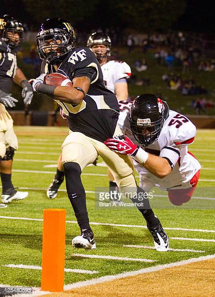 Running back Nick Knott of the Wake Forest Demon Deacons drags Tanner Burch of the GardnerWebb Bulldogs into the end zone on a 12yard touchdown run...