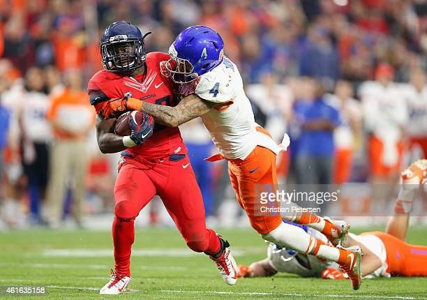 Running back Nick Wilson of the Arizona Wildcats is tackled by safety Darian Thompson of the Boise State Broncos after a reception during the second...