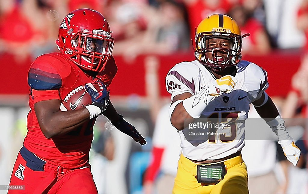 Running back Nick Wilson #28 of the Arizona Wildcats runs to score a 72 yard rushing touchdown in the third quarter during the Territorial Cup college football game against the Arizona State Sun Devils at Arizona Stadium on November 28, 2014 in Tucson, Arizona. The Wildcats defeated the Sun Devils 42-35 to win the PAC-12 south championship.