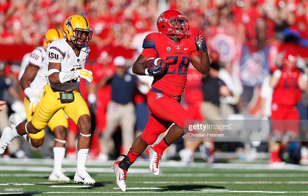 Running back Nick Wilson #28 of the Arizona Wildcats runs to score a 72-yard rushing touchdown in the third quarter during the Territorial Cup college football game against the Arizona State Sun Devils at Arizona Stadium on November 28, 2014 in Tucson, Arizona.
