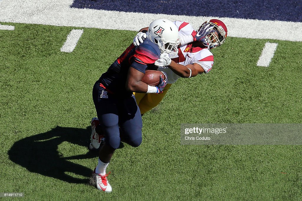 Running back Nick Wilson #28 of the Arizona Wildcats stiff arms defensive back Marvell Tell III #7 of the USC Trojans during the second quarter of the college football game at Arizona Stadium on October 15, 2016 in Tucson, Arizona. USC won 48-14.