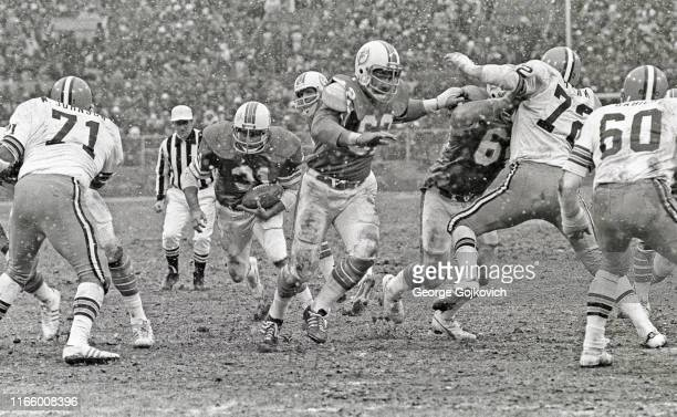 Running back Norm Bulaich of the Miami Dolphins runs behind the blocking of center Jim Langer and guard Bob Kuechenberg as defensive linemen Walter...