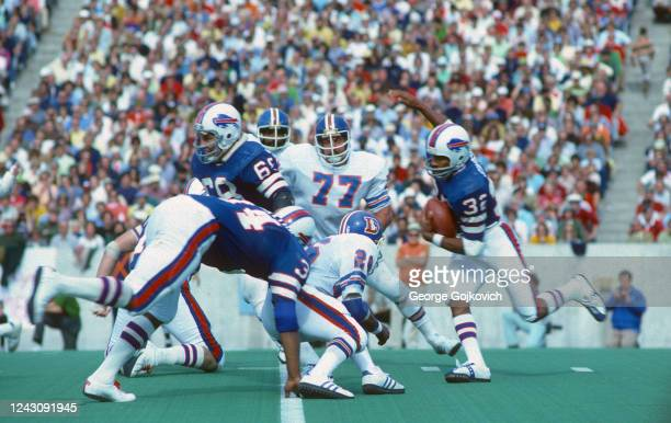 Running back OJ Simpson of the Buffalo Bills runs behind the blocking of offensive lineman Joe DeLamielleure and fullback Jim Braxton as he is...