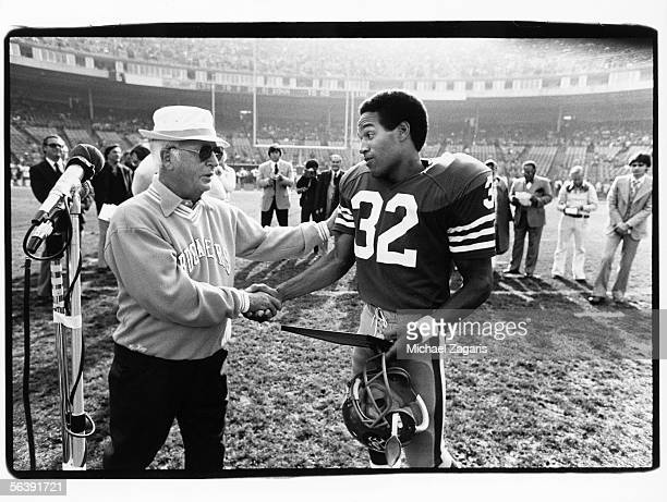 Running back OJ Simpson of the San Francisco 49ers shakes hands with John McKay his former coach at USC and current head coach of the Tampa Bay...