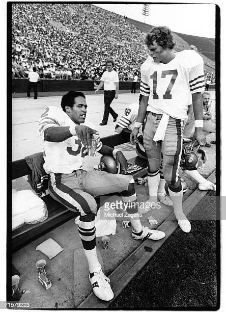 Running back OJ Simpson of the San Francisco 49ers talks to quarterback Steve DeBerg on the sideline during the game against the Los Angeles Rams at...