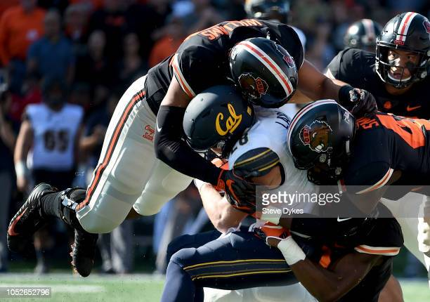 Running back Patrick Laird of the California Golden Bears is tackled by cornerback Dwayne Williams and linebacker Shemar Smith of the Oregon State...