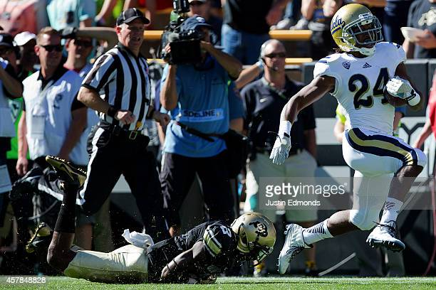 Running back Paul Perkins of the UCLA Bruins runs past cornerback Kenneth Crawley of the Colorado Buffaloes for a 93yard touchdown during the first...