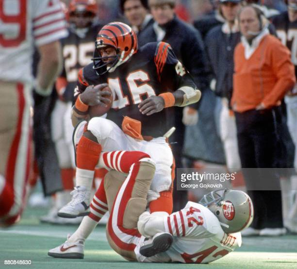 Running back Pete Johnson of the Cincinnati Bengals is tackled by safety Ronnie Lott of the San Francisco 49ers during a game at Riverfront Stadium...