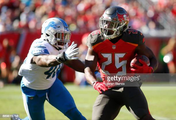 Running back Peyton Barber of the Tampa Bay Buccaneers evades linebacker Jarrad Davis of the Detroit Lions during a carry in the second quarter of an...