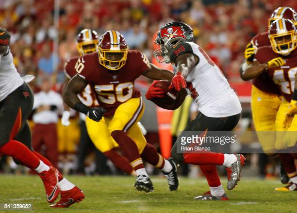 Running back Peyton Barber of the Tampa Bay Buccaneers gets pressure from outside linebacker Martrell Spaight of the Washington Redskins during a...