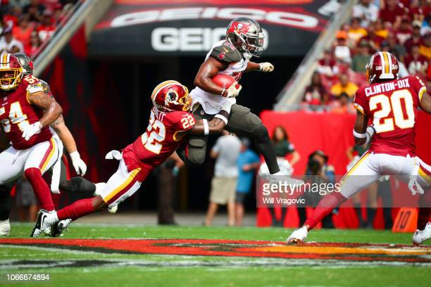 Running back Peyton Barber of the Tampa Bay Buccaneers hurdles past defensive back Deshazor Everett of the Washington Redskins for nine yards in the...