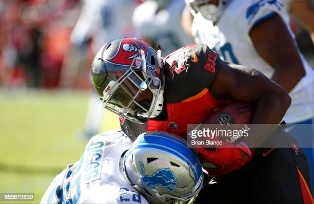 Running back Peyton Barber of the Tampa Bay Buccaneers is stopped by cornerback Quandre Diggs of the Detroit Lions during a carry in the second...