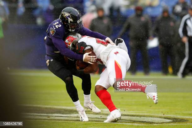 Running Back Peyton Barber of the Tampa Bay Buccaneers is tackled by free safety Eric Weddle of the Baltimore Ravens in the first quarter at MT Bank...