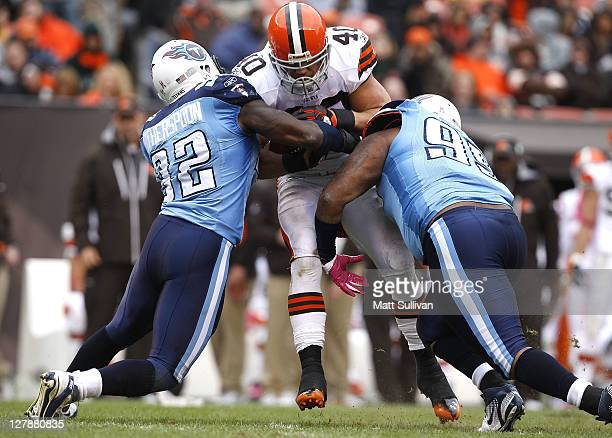 Running back Peyton Hillis of the Cleveland Browns is tackled by defenders Will Witherspoon and William Hayes of the Tennessee Titans at Cleveland...
