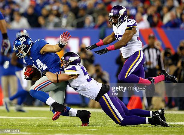 Running back Peyton Hillis of the New York Giants is tackled by outside linebacker Chad Greenway and strong safety Jamarca Sanford of the Minnesota...