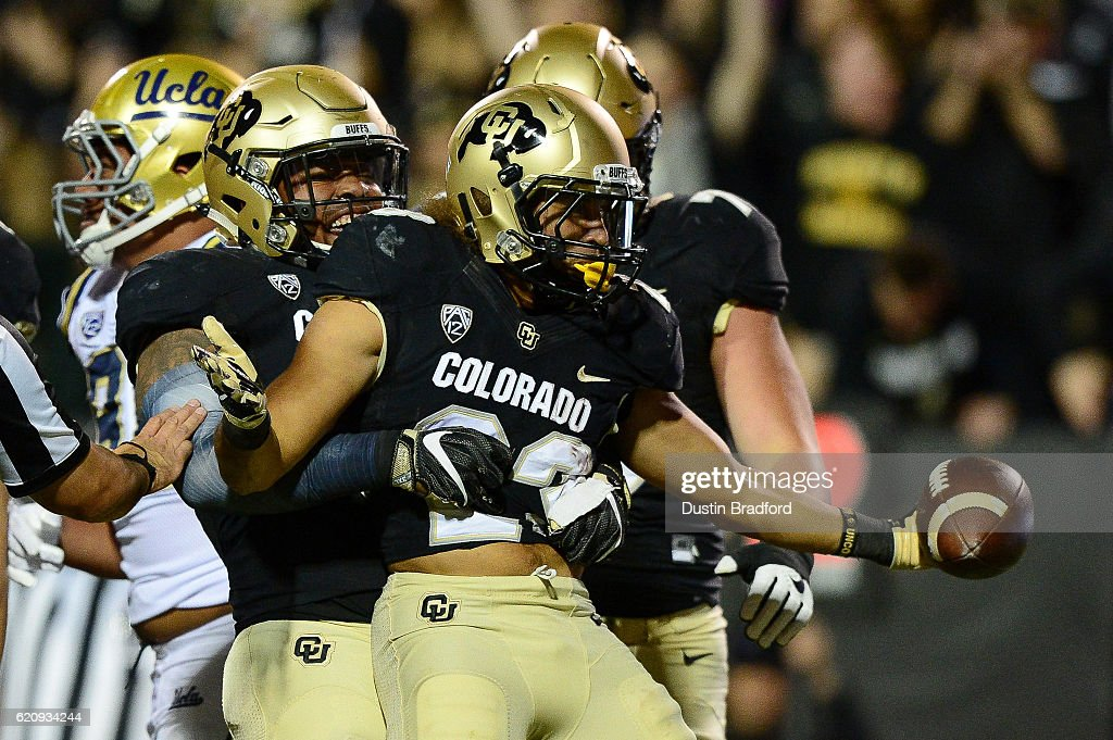 Running back Phillip Lindsay #23 of the Colorado Buffaloes celebrates a touchdown with tight end George Frazier #5 in the first quarter of a game against the UCLA Bruins at Folsom Field on November 3, 2016 in Boulder, Colorado.