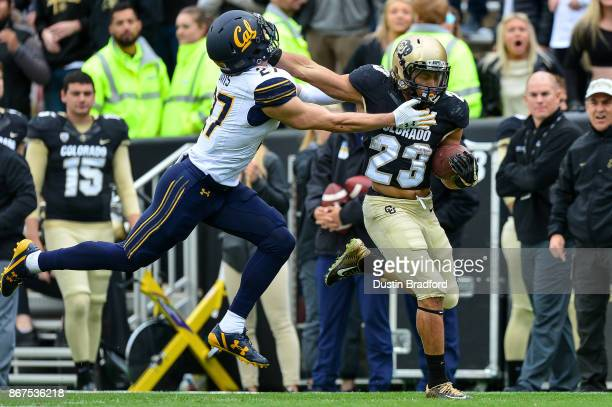 Running back Phillip Lindsay of the Colorado Buffaloes gives a stiff arm to cornerback Ashtyn Davis of the California Golden Bears on a long run in...
