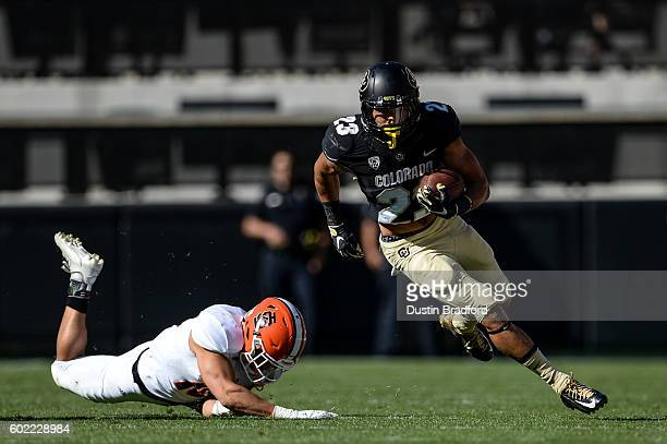 Running back Phillip Lindsay of the Colorado Buffaloes rushes and breaks a tackle by defensive back Taison Manu of the Idaho State Bengals in the...