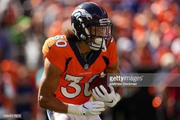 Running back Phillip Lindsay of the Denver Broncos carries the ball against the Oakland Raiders in the first quarter of a game at Broncos Stadium at...