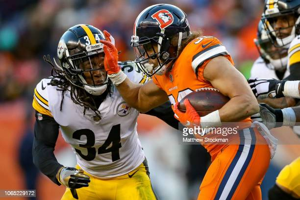 Running back Phillip Lindsay of the Denver Broncos carries the ball against Terrell Edmunds of the Pittsburgh Steelers in the third quarter of a game...