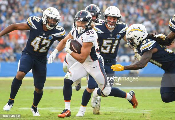 Running back Phillip Lindsay of the Denver Broncos runs as he's chased by strong safety Jahleel Addae of the Los Angeles Chargers in the third...