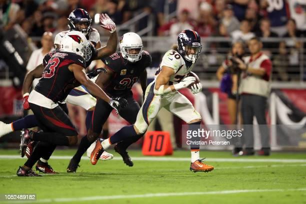 Running back Phillip Lindsay of the Denver Broncos runs past cornerback Patrick Peterson and linebacker Haason Reddick of the Arizona Cardinals for a...
