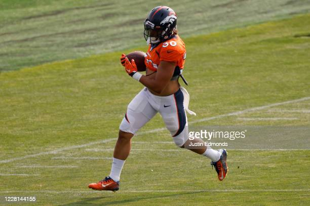 Running back Phillip Lindsay of the Denver Broncos runs with the football during a training session at UCHealth Training Center on August 21, 2020 in...