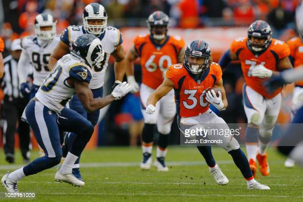 Running back Phillip Lindsay of the Denver Broncos runs with the football as safety Lamarcus Joyner of the Los Angeles Rams defends on the play...