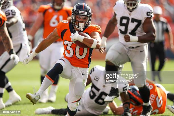 Running back Phillip Lindsay of the Denver Broncos rushes against the Oakland Raiders at Broncos Stadium at Mile High on September 16 2018 in Denver...