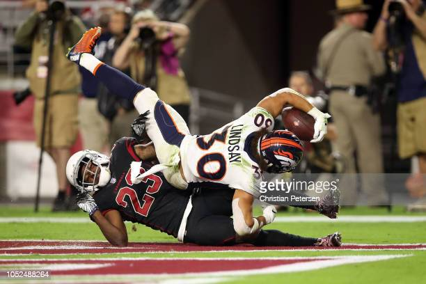 Running back Phillip Lindsay of the Denver Broncos scores a 28yard touchdown over defensive back Bene' Benwikere of the Arizona Cardinals during the...