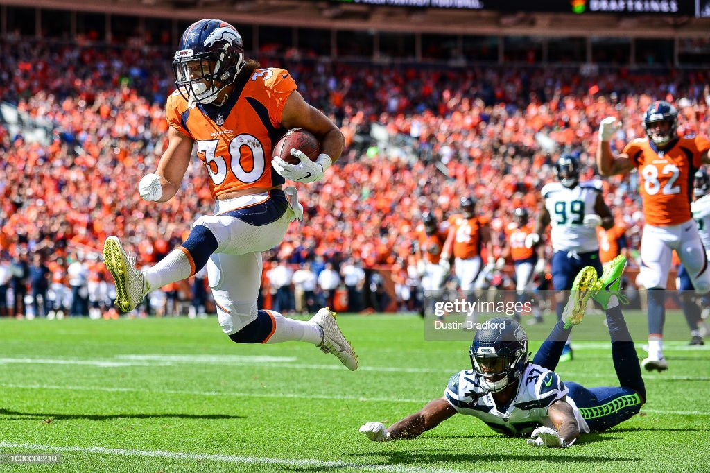 Running back Phillip Lindsay #30 of the Denver Broncos scores a first quarter touchdown on a reception as cornerback Tre Flowers #37 of the Seattle Seahawks falls to the ground during a game at Broncos Stadium at Mile High on September 9, 2018 in Denver, Colorado.