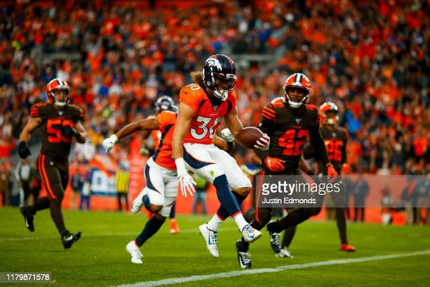 Running back Phillip Lindsay of the Denver Broncos scores a touchdown as safety Morgan Burnett of the Cleveland Browns looks on during the third...