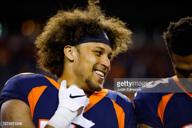Running back Phillip Lindsay of the Denver Broncos smiles as he stands on the field before a game against the Cleveland Browns at Broncos Stadium at...