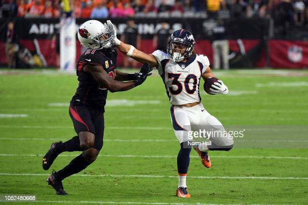 Running back Phillip Lindsay of the Denver Broncos stiff arms cornerback Patrick Peterson of the Arizona Cardinals during the first quarter at State...