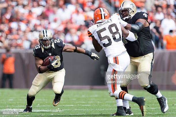 Running back Pierre Thomas caries the ball as he avoids a tackle by outside linebacker Christian Kirksey of the Cleveland Browns who is being blocked...