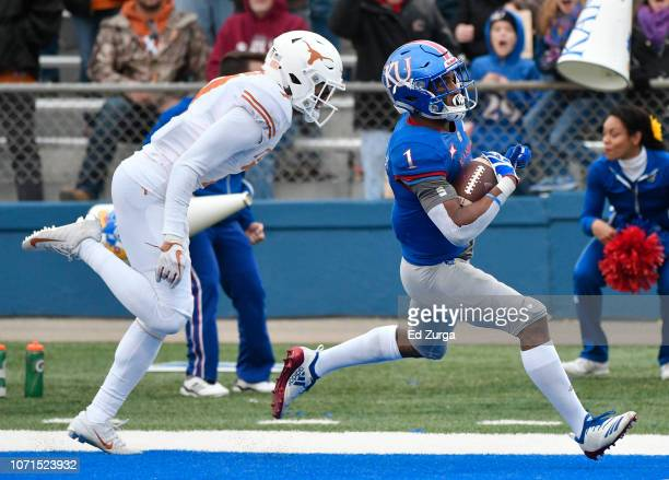 Running back Pooka Williams Jr #1 of the Kansas Jayhawks goes in for a 57yard touchdown run against defensive back Caden Sterns of the Texas...