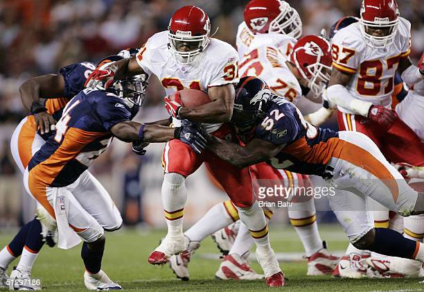 Running back Priest Holmes of the Kansas City Chiefs gets stopped running through a hole by cornerback Champ Bailey and linebacker DJ Williams of the...