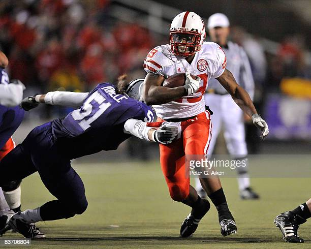 Running back Quentin Castille of the Nebraska Cornhuskers brakes the tackle of linebacker Ulla Pomele of the Kansas State Wildcats enroute to a first...