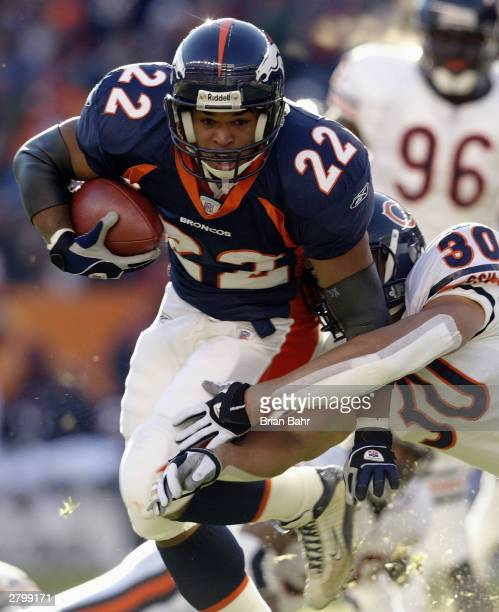 Running back Quentin Griffin of the Denver Broncos runs the ball as safety Mike Brown of the Chicago Bears attempts a tackle on November 23 2003 at...