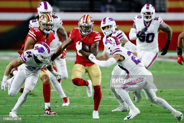 Running back Raheem Mostert of the San Francisco 49ers rushes the football past cornerback Taron Johnson and strong safety Micah Hyde of the Buffalo...