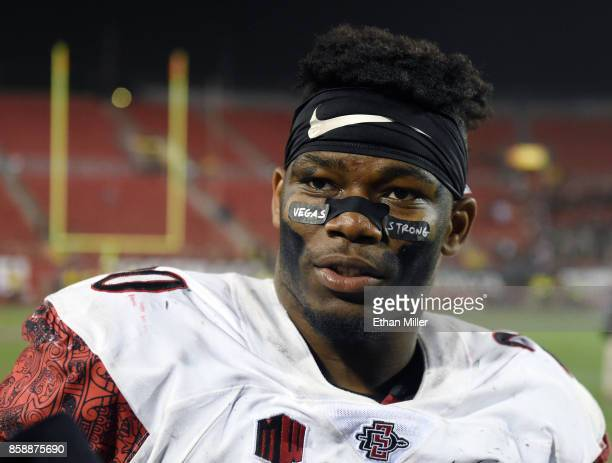 """Running back Rashaad Penny of the San Diego State Aztecs wears eye black stickers with the words """"Vegas Strong"""" on them as he is interviewed on the..."""